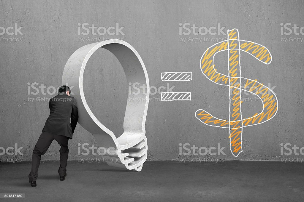 Businessman pushing granite lightbulb shape with dollar sign stock photo