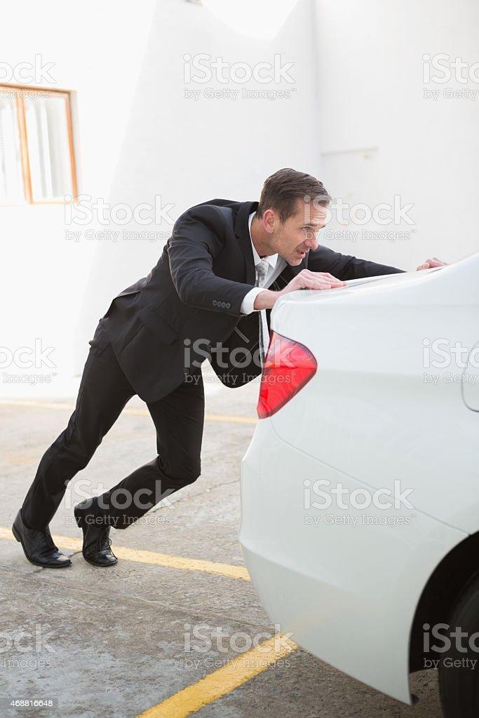 Businessman pushing his broken down car stock photo