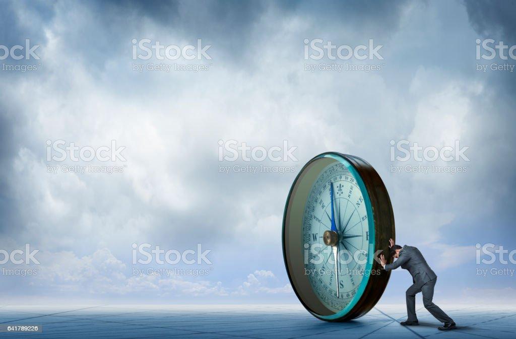 Businessman Pushing Large Compass Across Generic Map stock photo