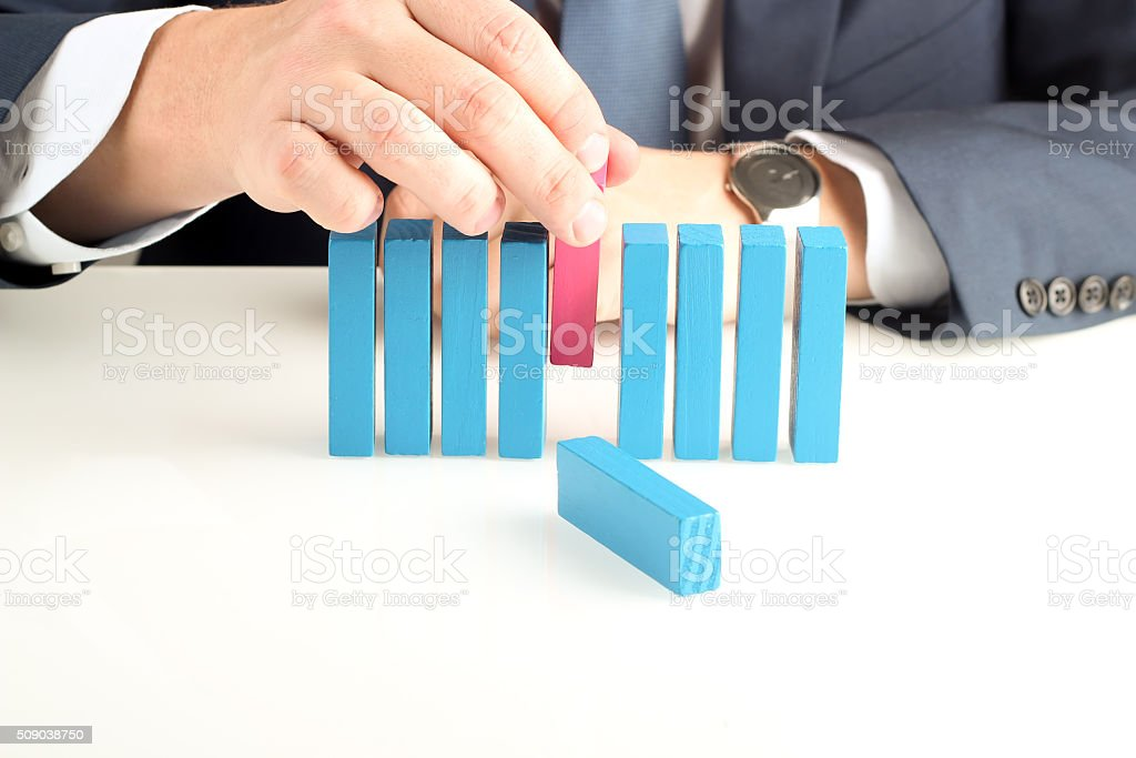 Businessman pushing out  wooden block With Hand At Desk stock photo