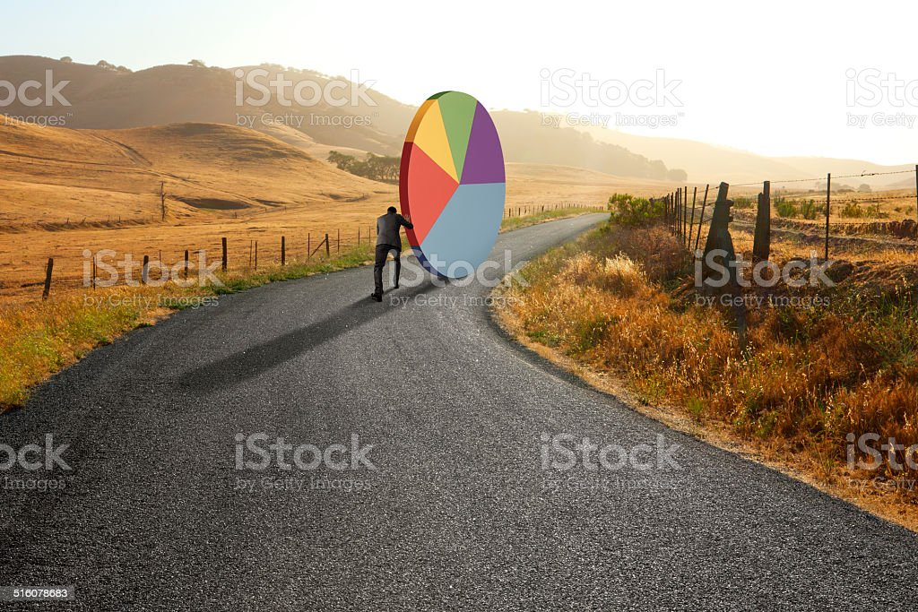 Businessman pushing pie chart down rural road stock photo