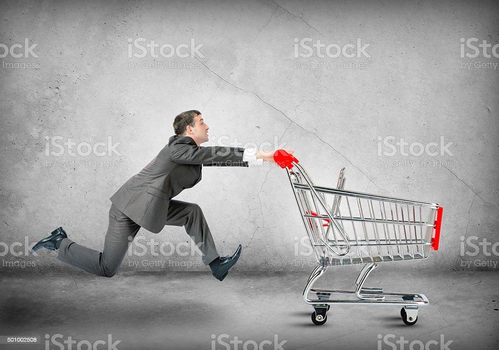 Businessman pushing shopping cart stock photo