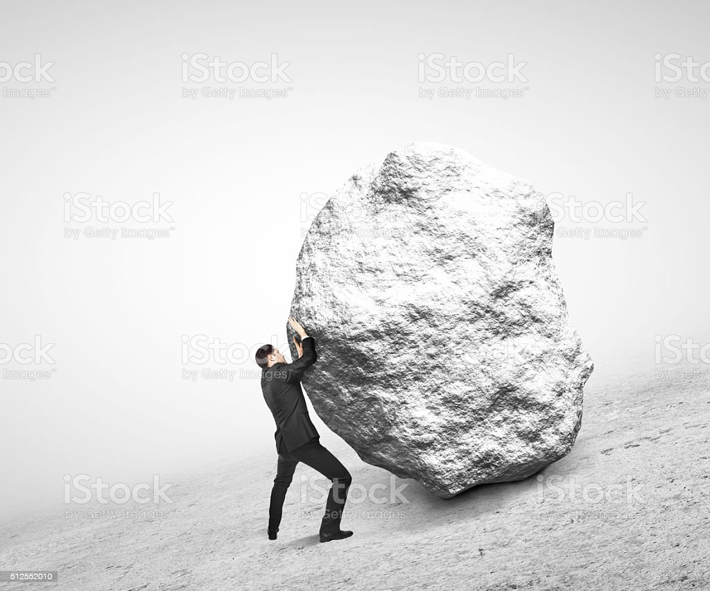 businessman pushing stone stock photo