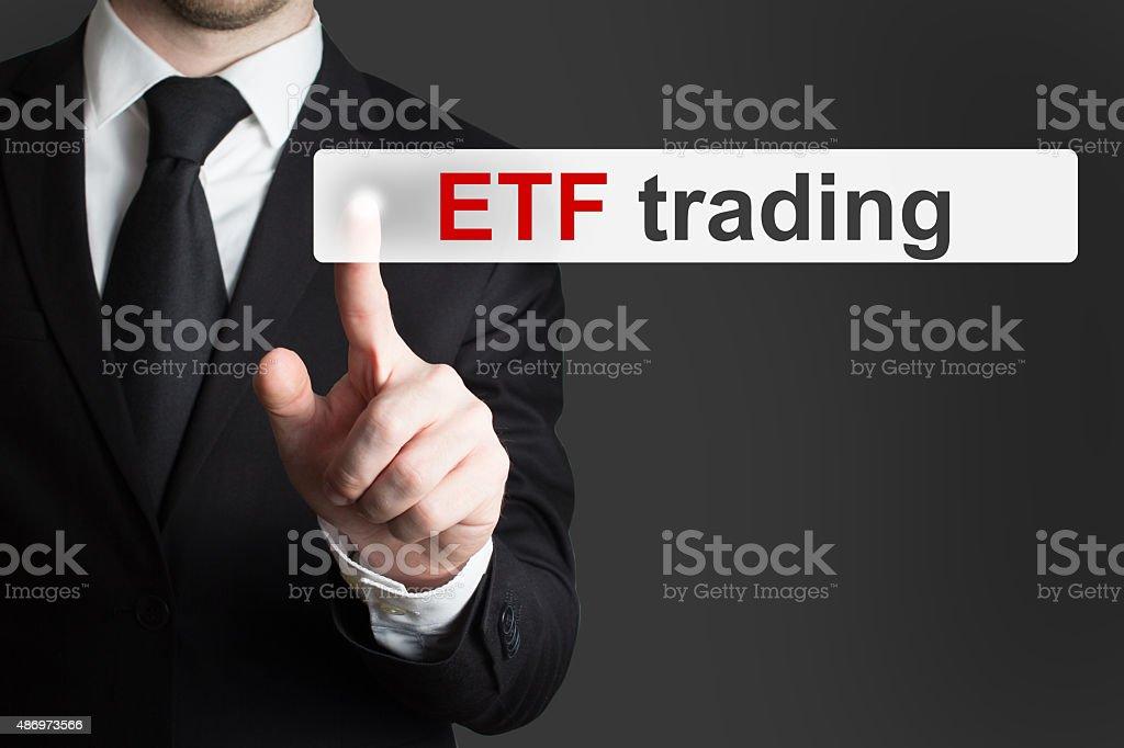 businessman pushing touchscreen button etf trading stock photo