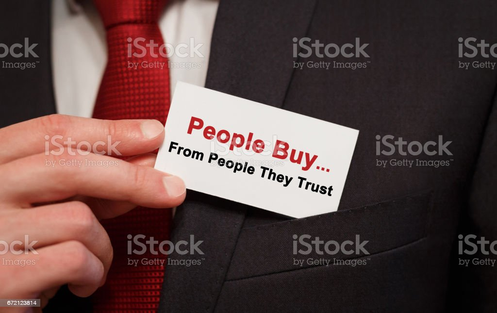 Businessman putting a card with text People Buy From People They Trust in the pocket stock photo