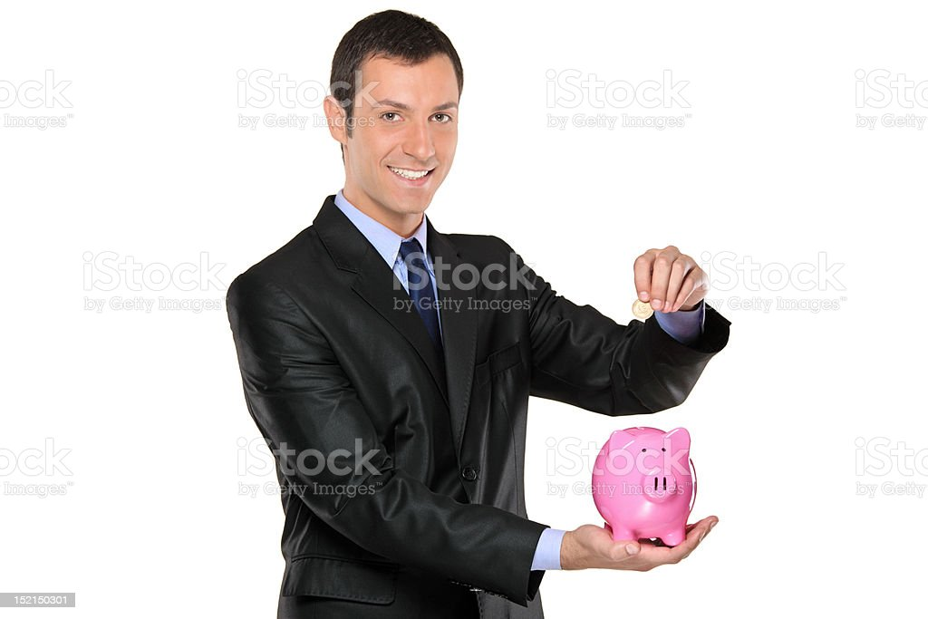 Businessman putting a coin into piggy bank royalty-free stock photo