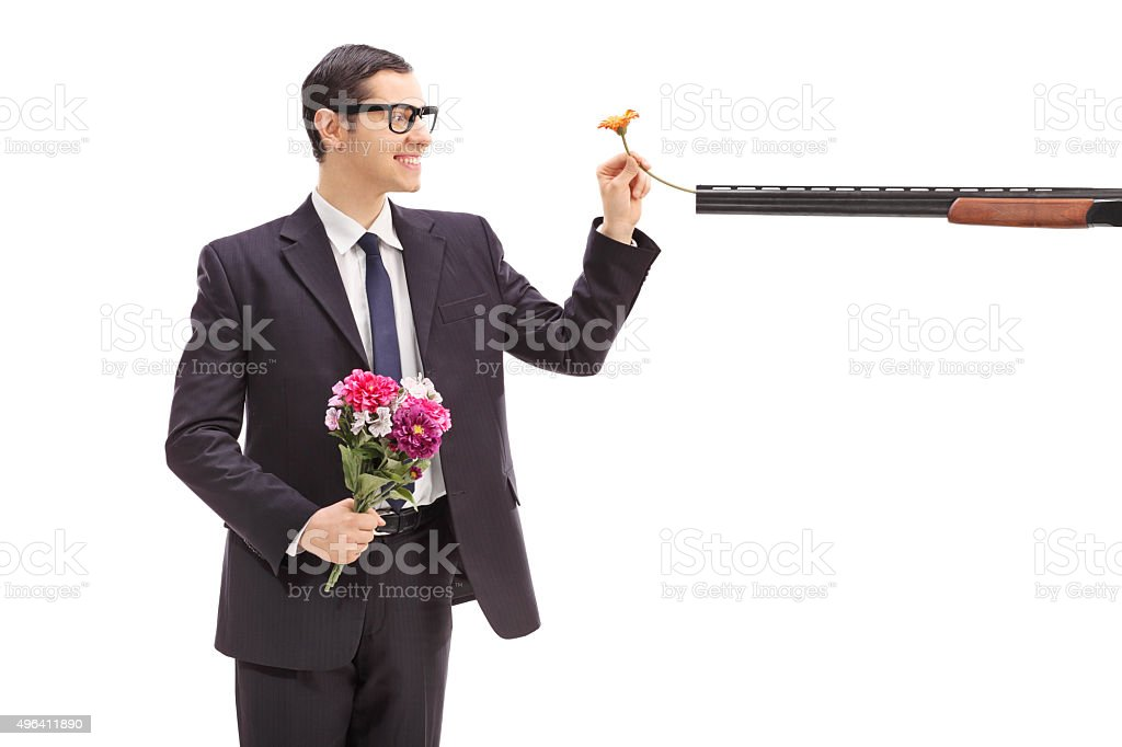 Businessman putting a flower in a rifle stock photo