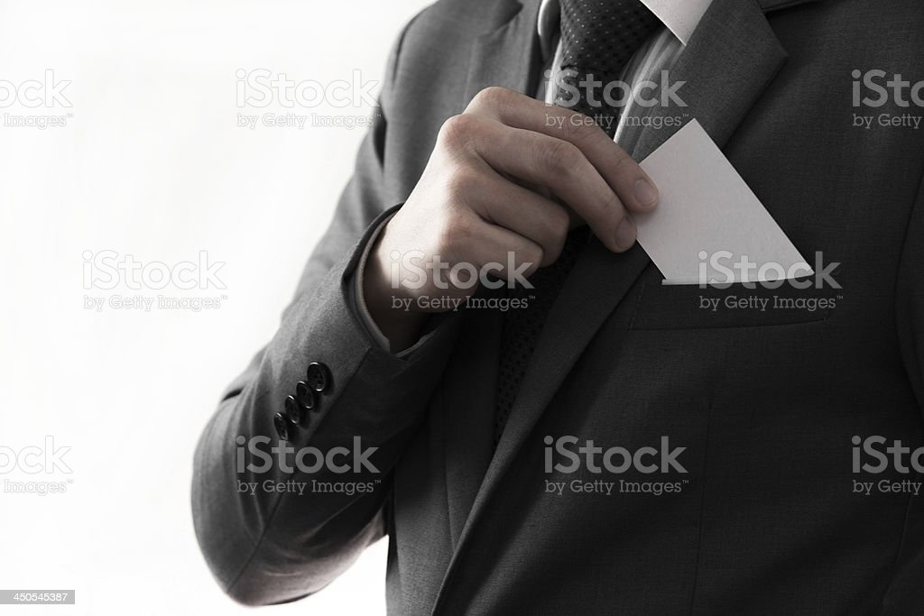 Businessman putting blank card in his pocket stock photo