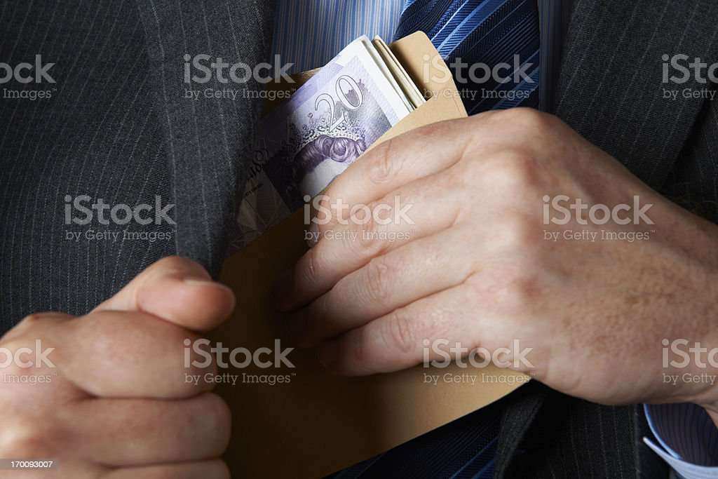 Businessman Putting Envelope Filled With Sterling In Jacket Pocket stock photo