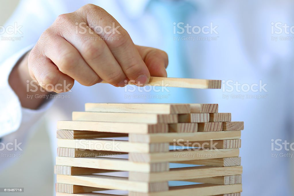 Businessman putting last block to the tower stock photo