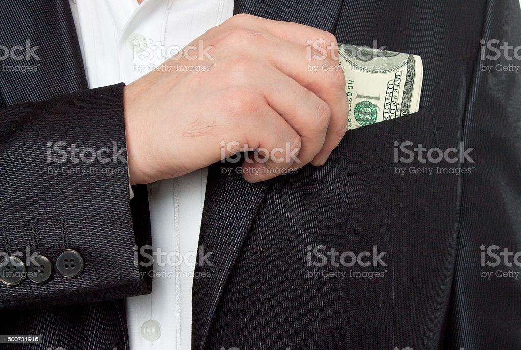 businessman putting money in pocket costume stock photo