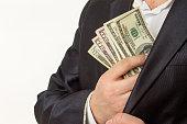 Businessman putting money in suit jacket pocket