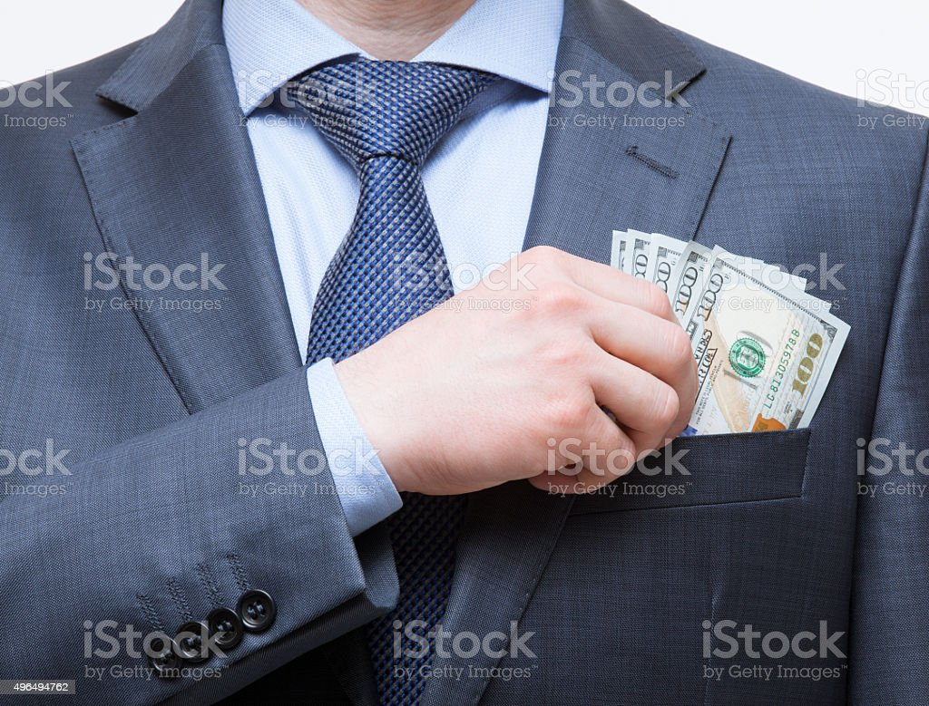 Businessman putting money in the breast pocket stock photo