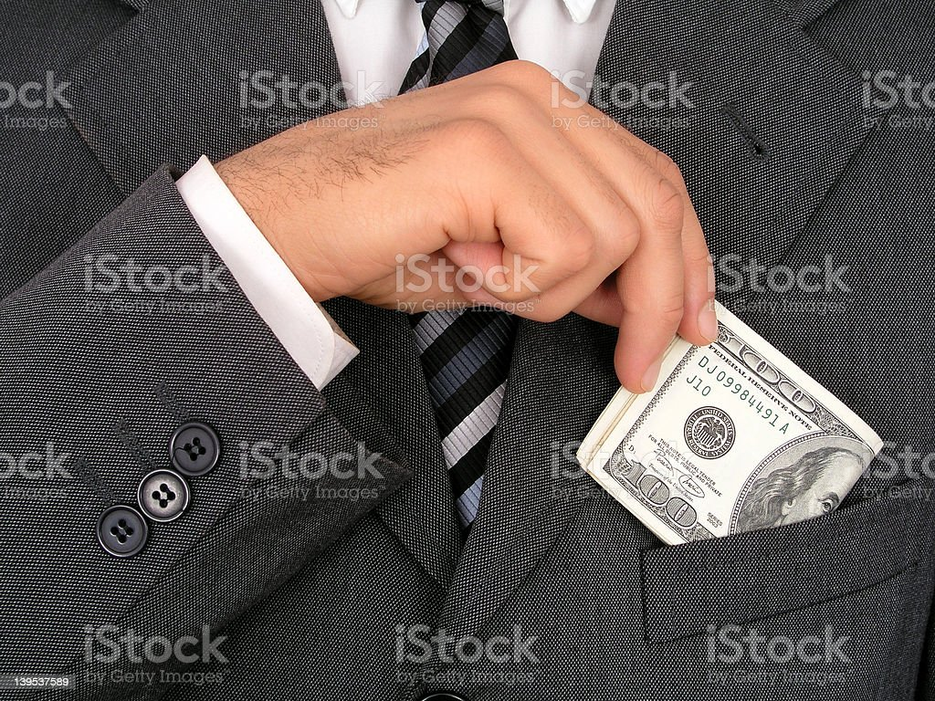 Businessman Putting Money Into Pocket stock photo