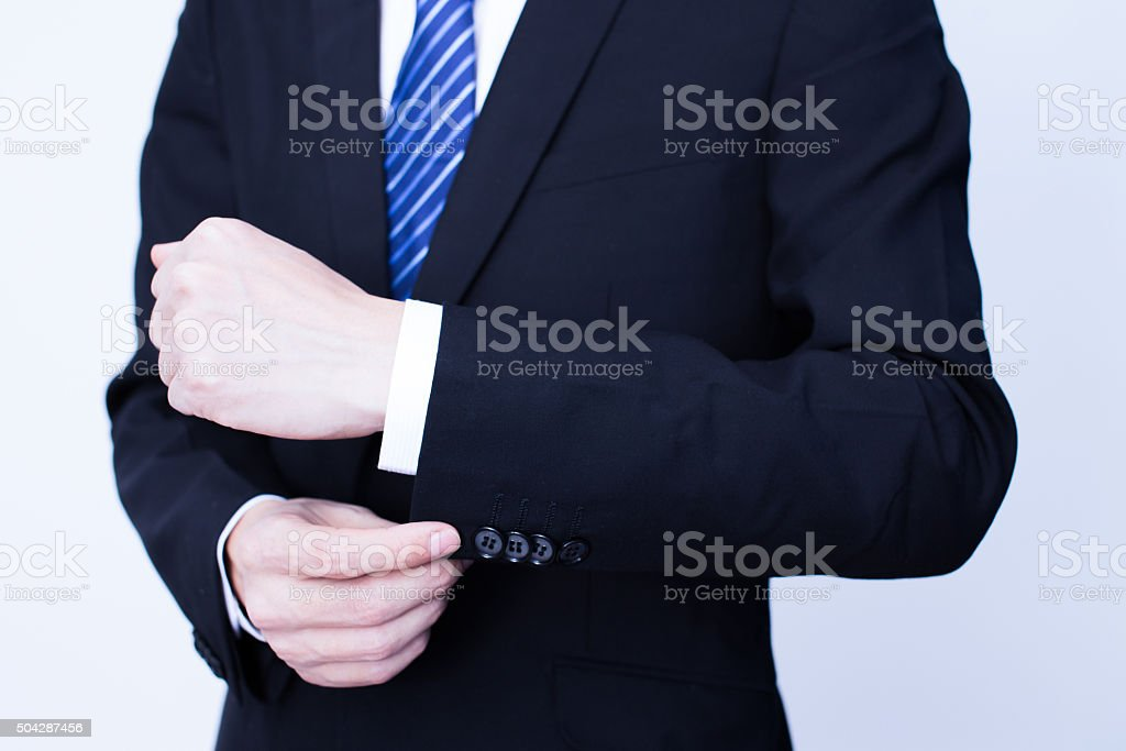 Businessman putting on cuff-links as he gets dressed stock photo