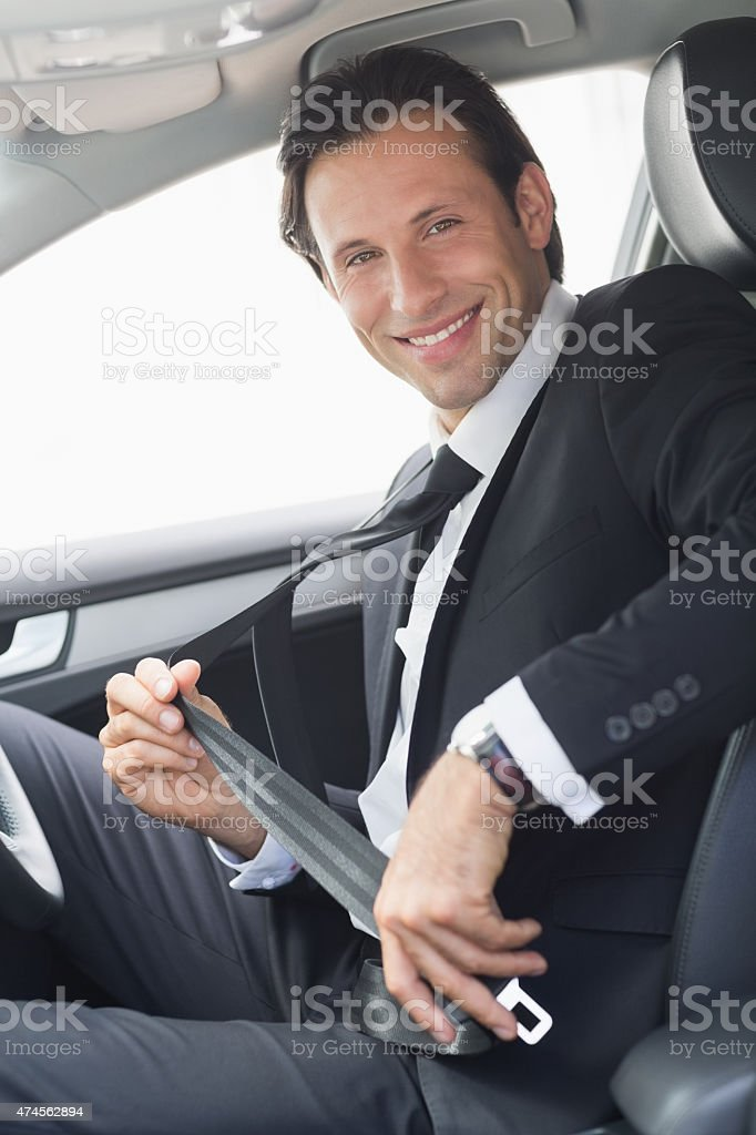 Businessman putting on his seat belt stock photo
