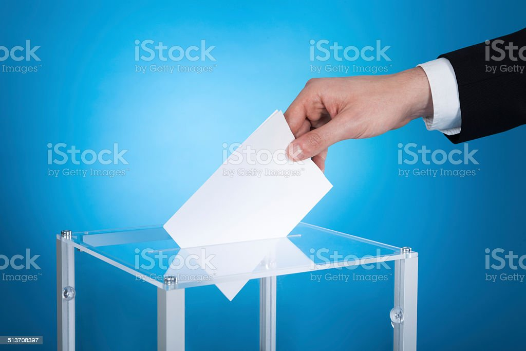Businessman Putting Paper In Election Box stock photo