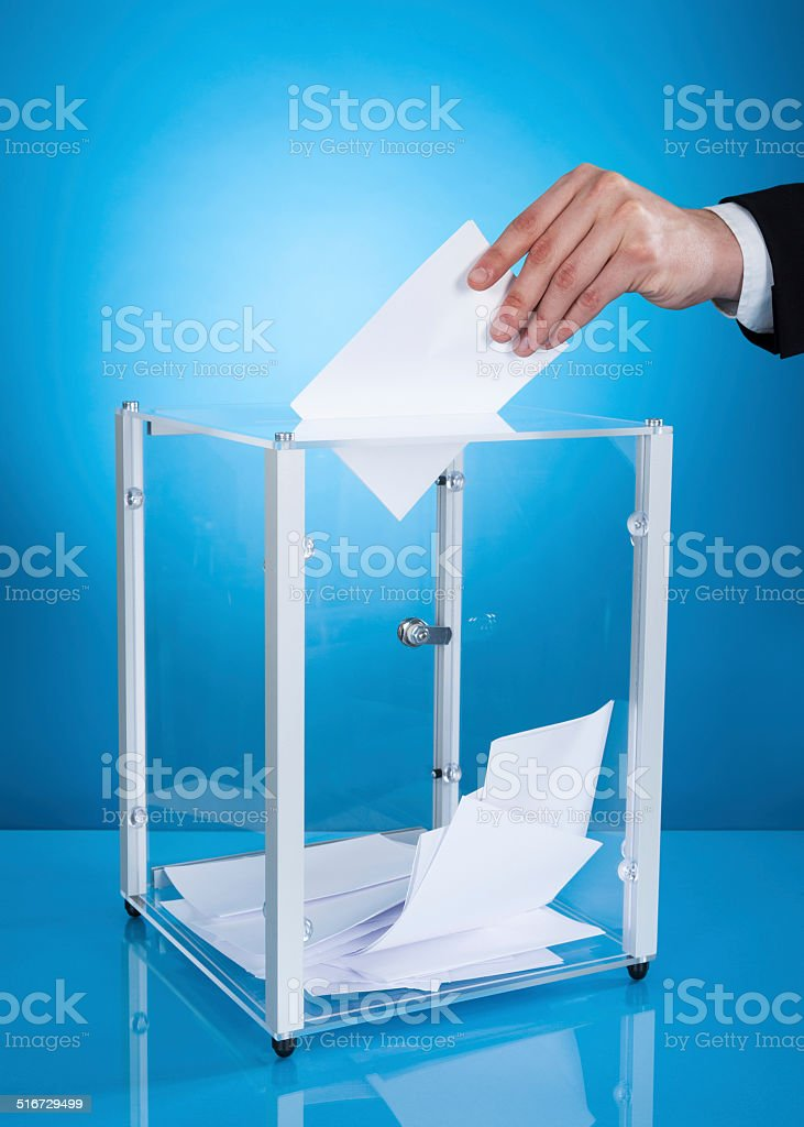 Businessman Putting Paper In Polling Box stock photo