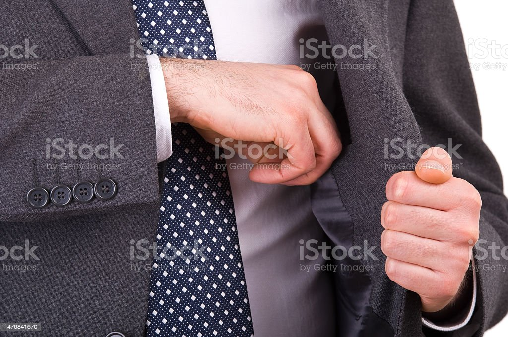 Businessman putting something in his pocket. stock photo