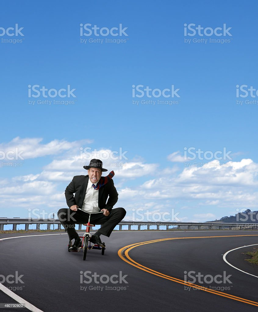 Businessman Racing On A Tricycle stock photo