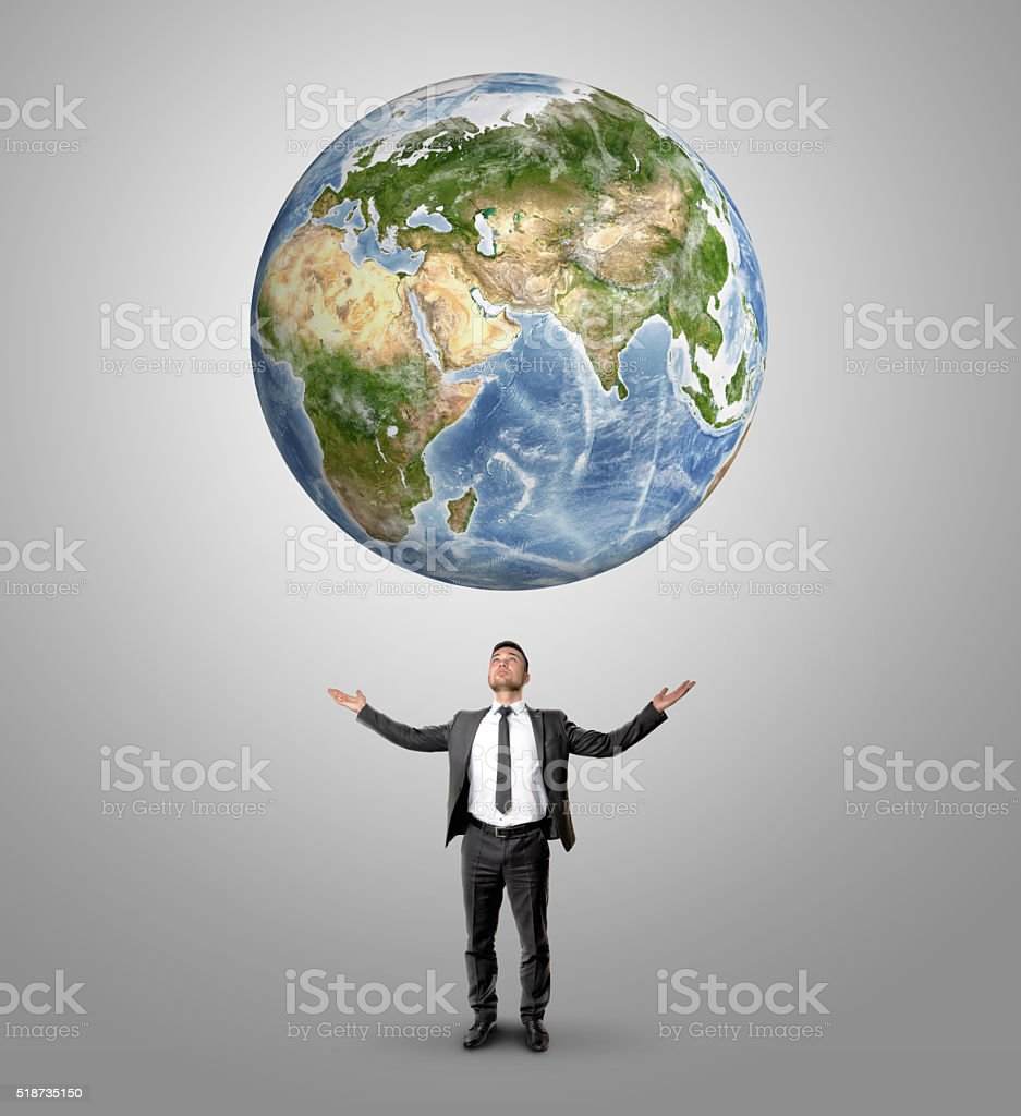 Businessman raised his hands to hold Earth looking at it stock photo