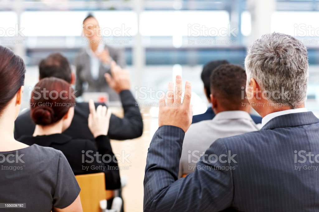 Businessman Raising His Hand at a Conference royalty-free stock photo