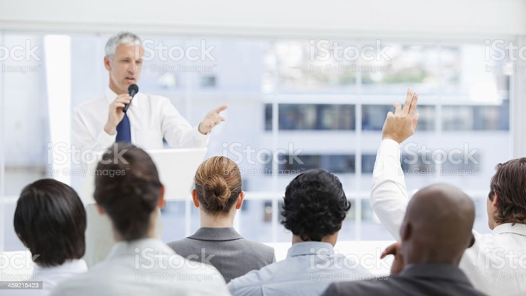 Businessman raising his hand while looking at a colleague royalty-free stock photo