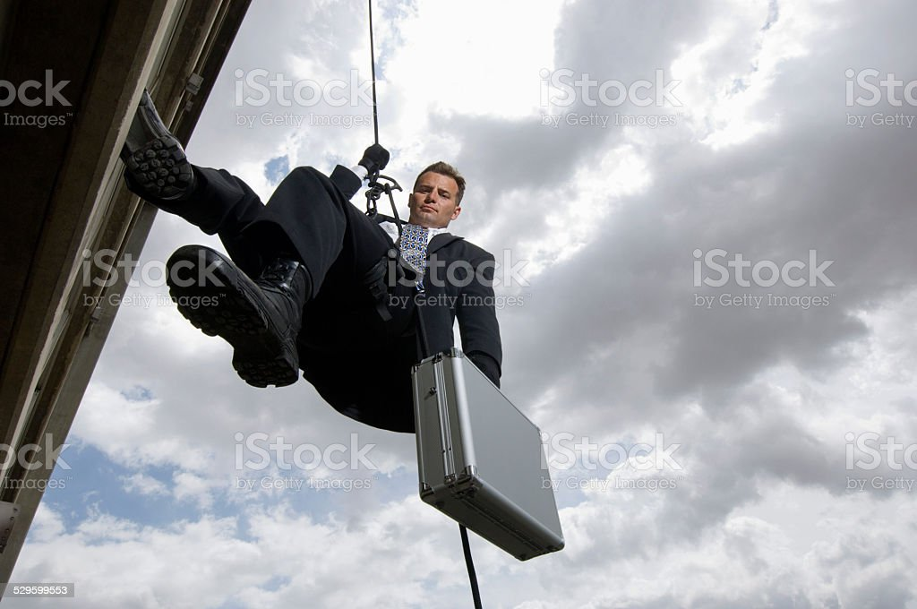 Businessman Rappelling Down By Rope stock photo