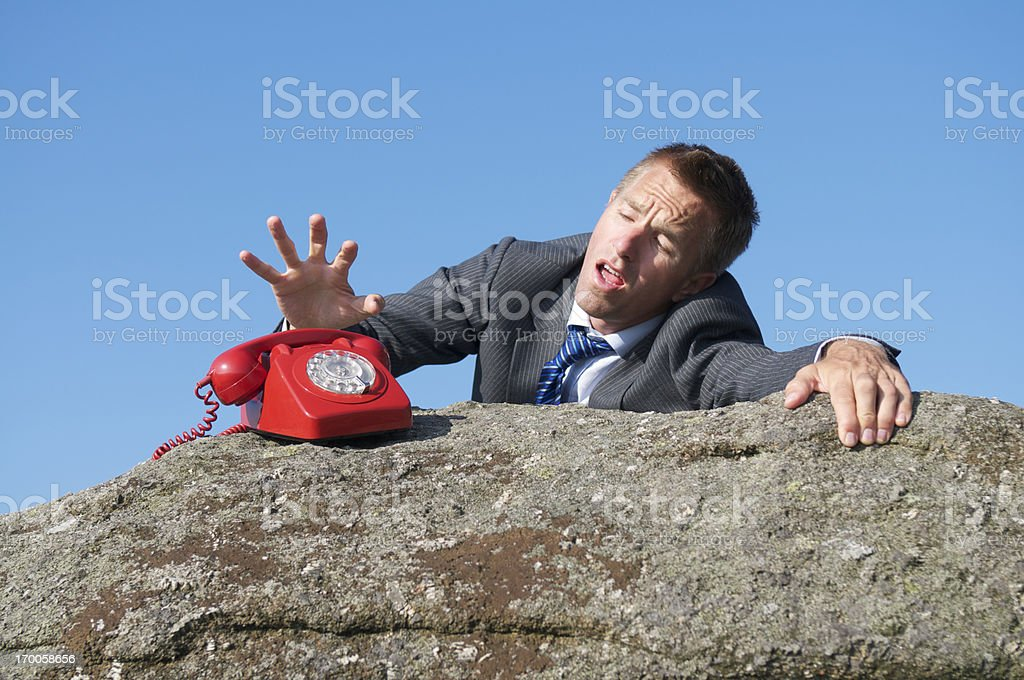 Businessman Reaches to Make Desperate Call from Cliff stock photo