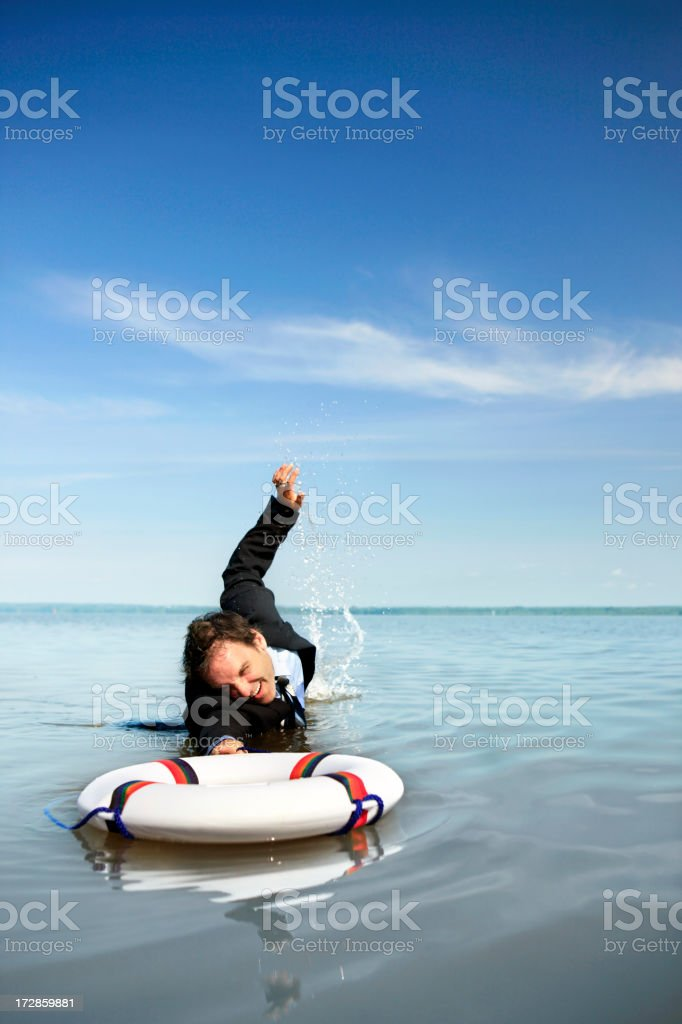 Businessman reaching for a life belt royalty-free stock photo