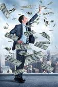 Businessman Reaching For Money Falling From Sky