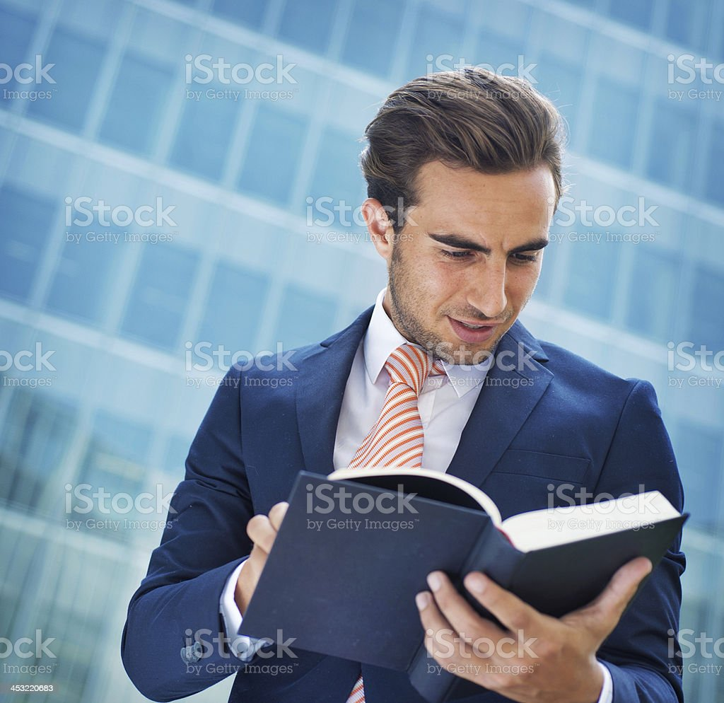 Businessman reading a book in Front of his Office stock photo