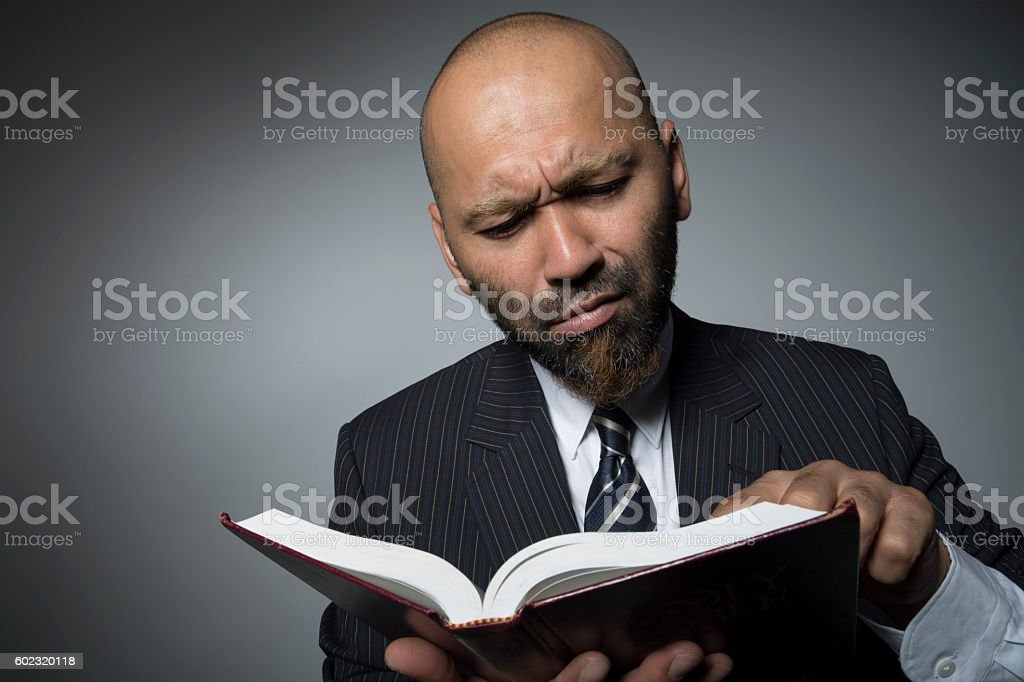 Businessman reading a book with a serious face. stock photo