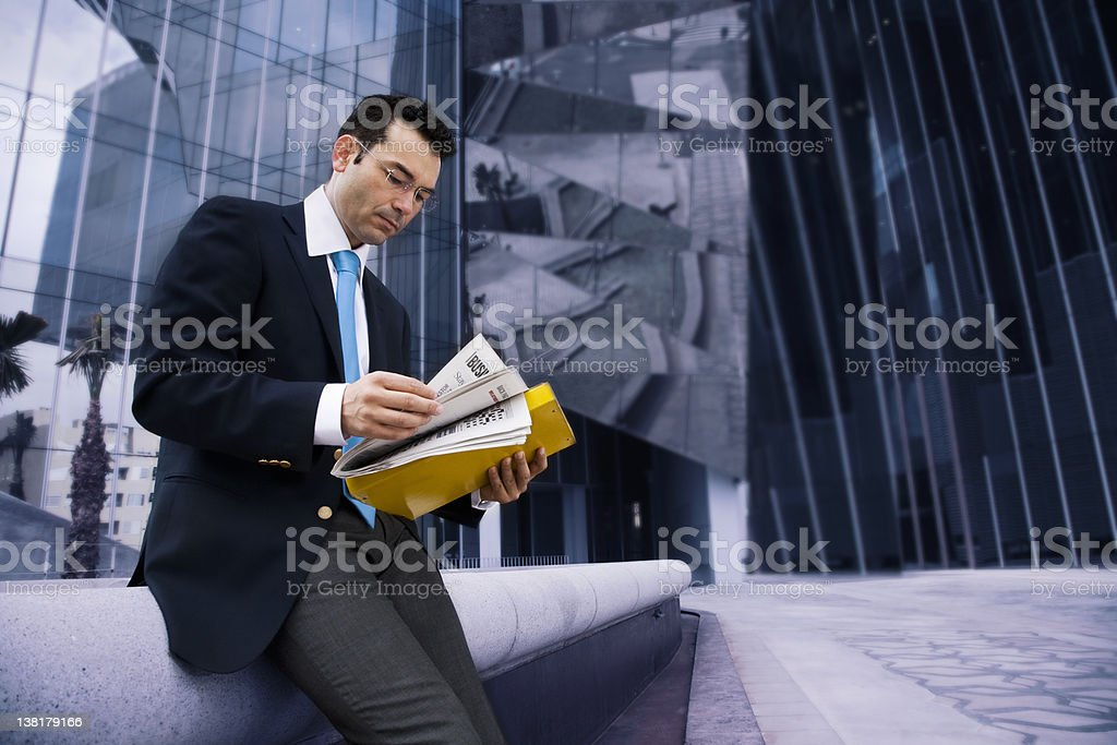 Businessman reading a  financial newspaper royalty-free stock photo