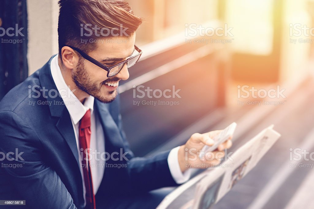 Businessman reading a newspaper at the street stock photo