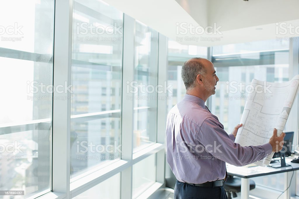 Businessman reading blueprint in office royalty-free stock photo