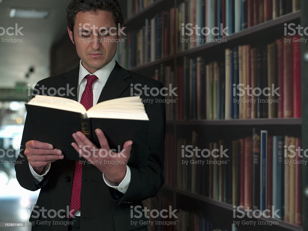 Businessman reading book in library stock photo