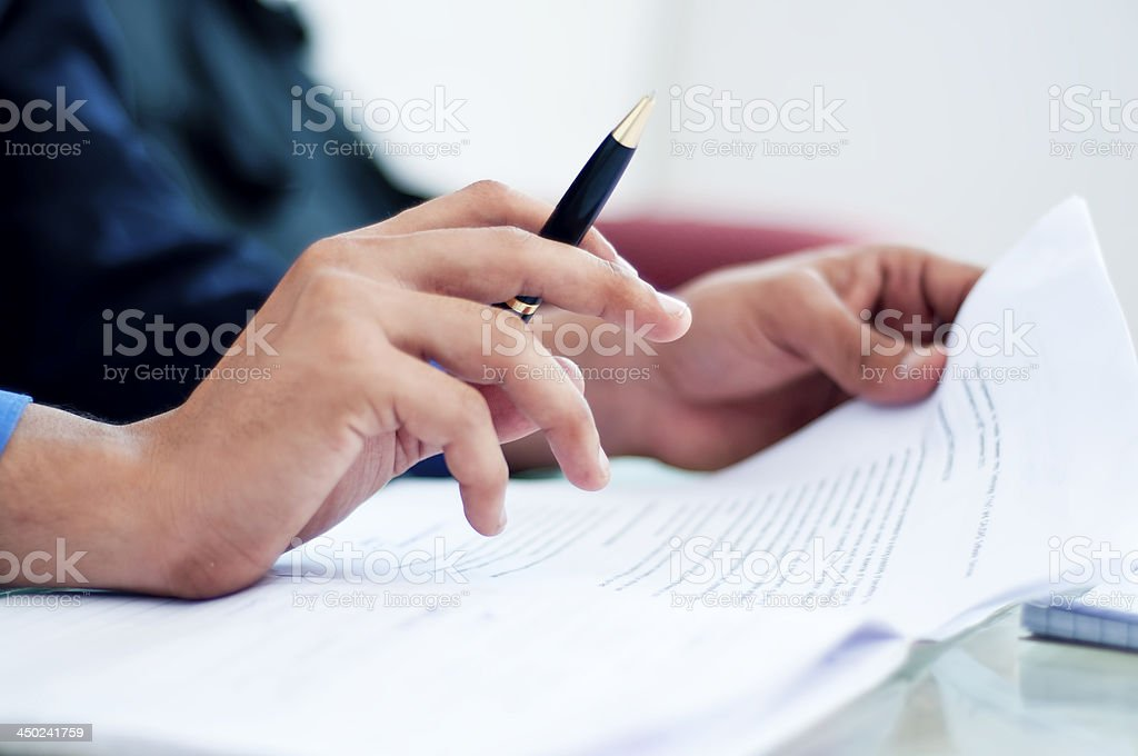 Businessman reading contract before signing stock photo