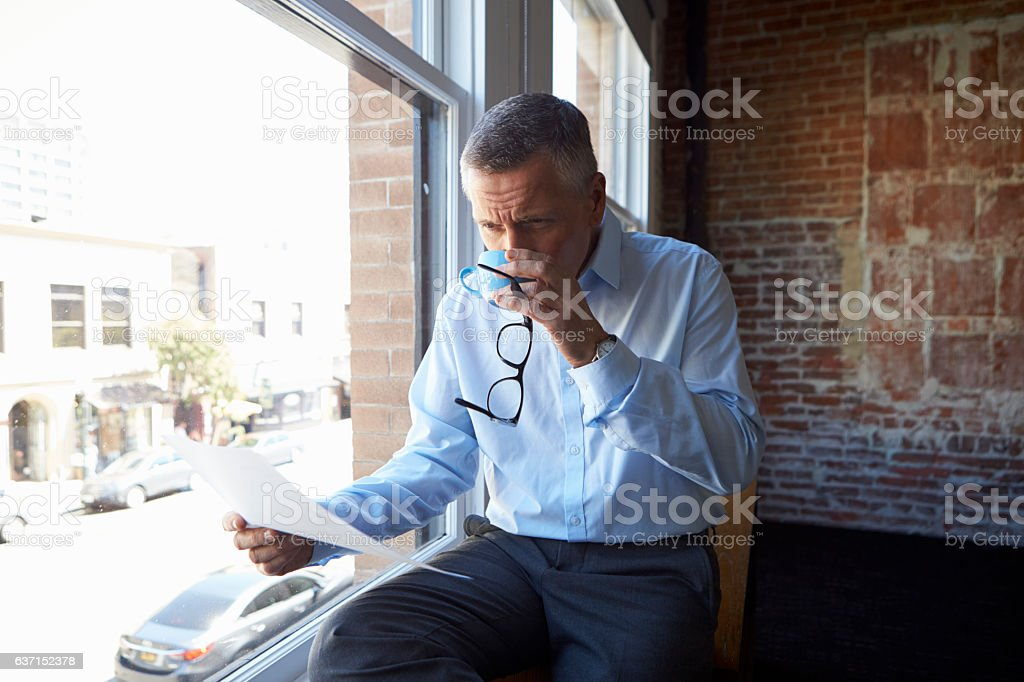 Businessman Reading Document Sitting By Office Window stock photo