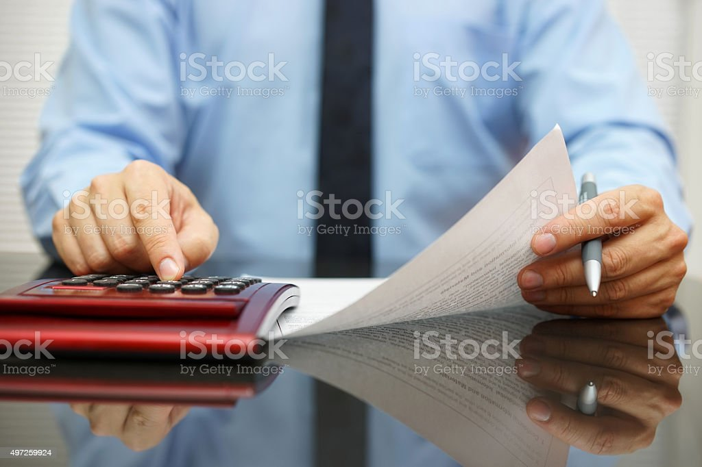 businessman reading  document with numbers and calculating stock photo
