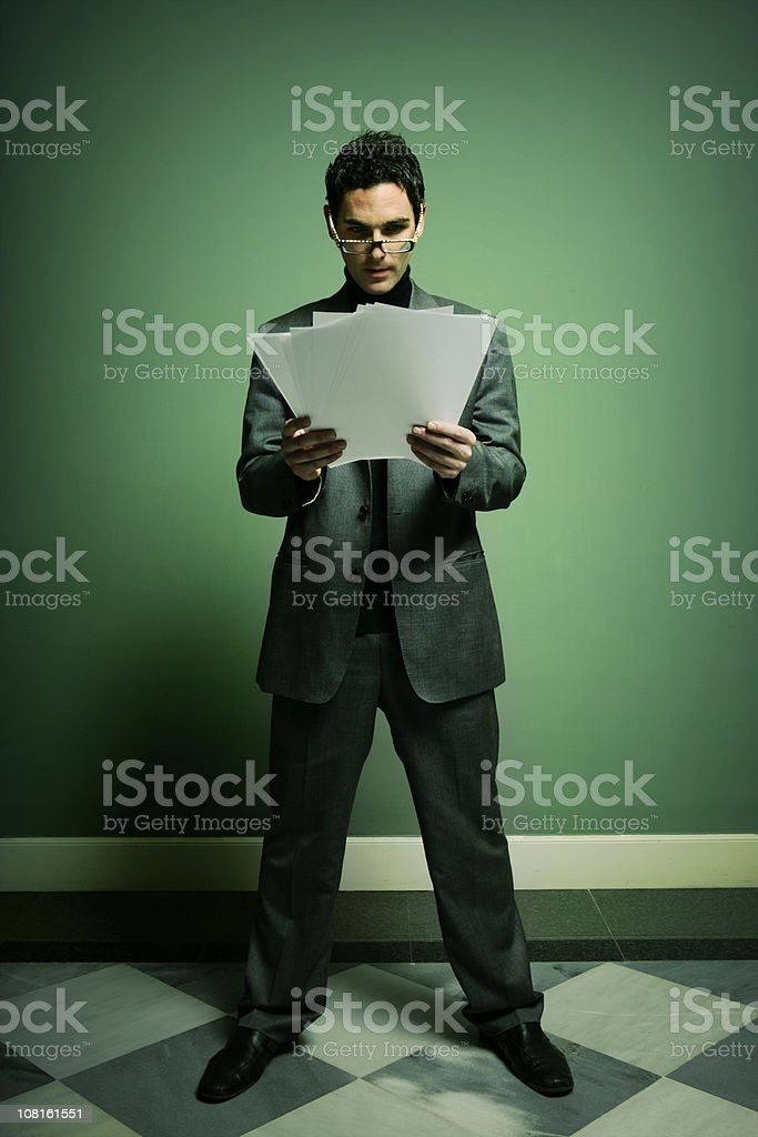 Businessman Reading Documents and Standing in Hallway royalty-free stock photo