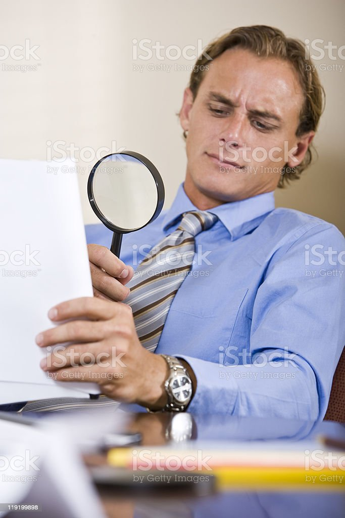 Businessman reading fine print in contract with magnifying glass stock photo