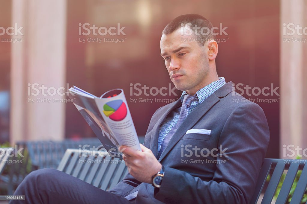 Businessman reading magazine outdoors stock photo