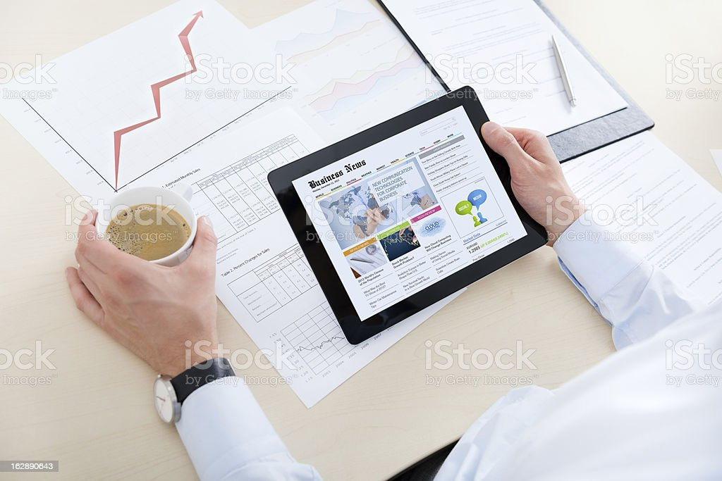 Businessman reading news on web stock photo