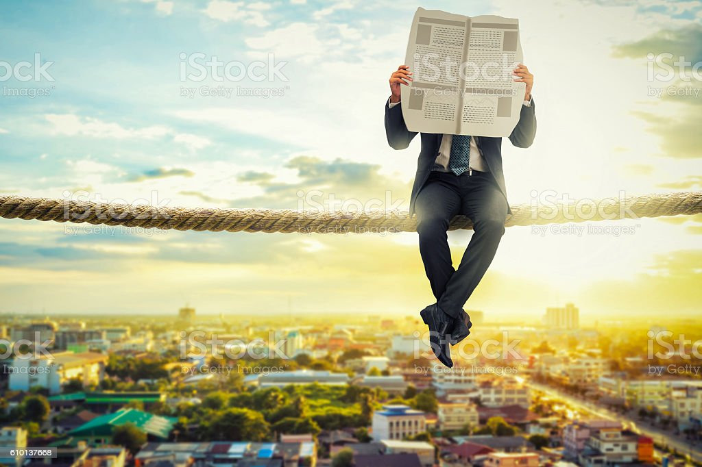 businessman reading news paper on rope in the morning stock photo
