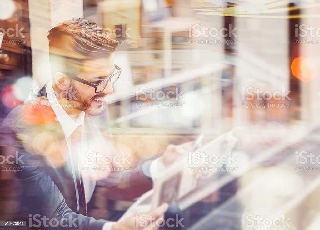 Businessman reading newspaper and texting stock photo