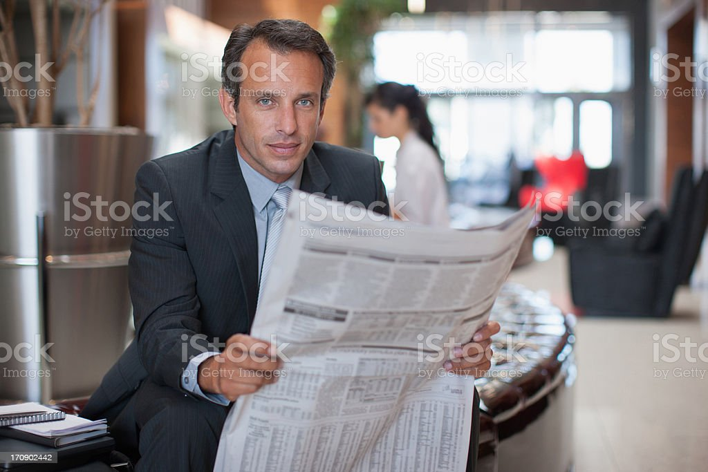 Businessman reading newspaper in hotel lobby royalty-free stock photo