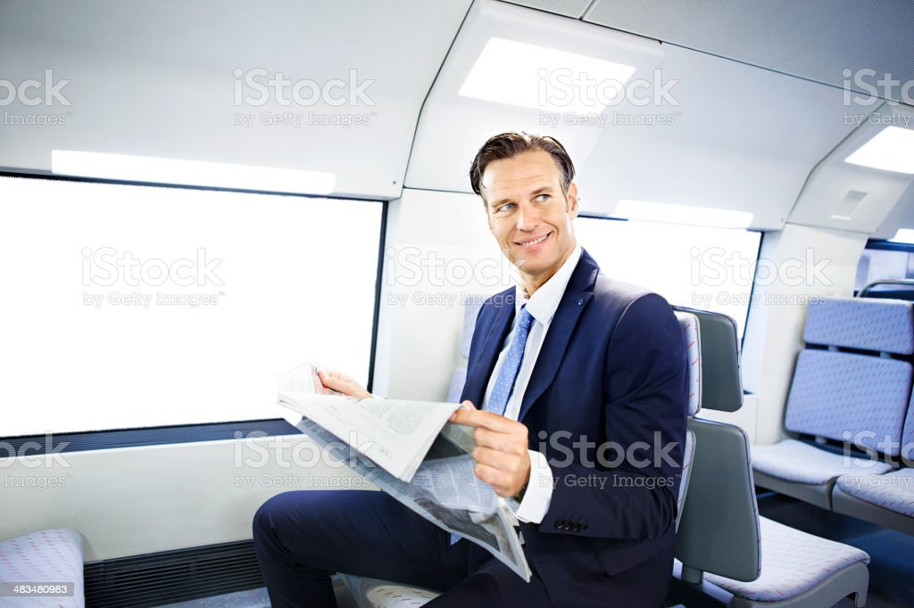 Businessman reading newspaper on train royalty-free stock photo