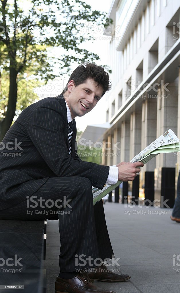 Businessman reading newspaper outdoors royalty-free stock photo