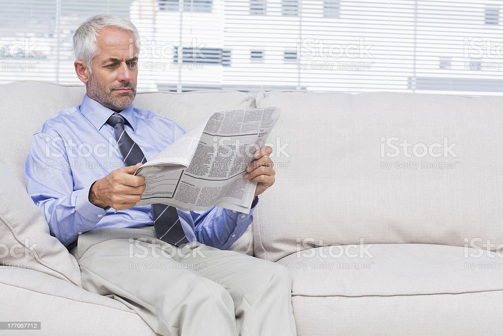 Businessman reading newspaper royalty-free stock photo